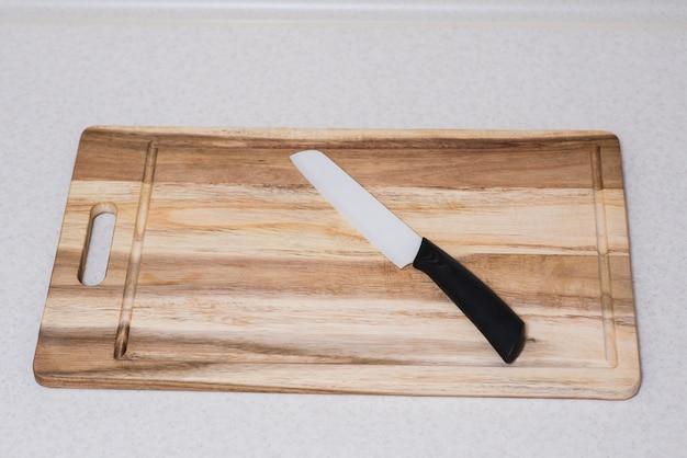Zerkratztes holzschneidebrett und keramikmesser auf dem tisch in der küche. ansicht von oben.