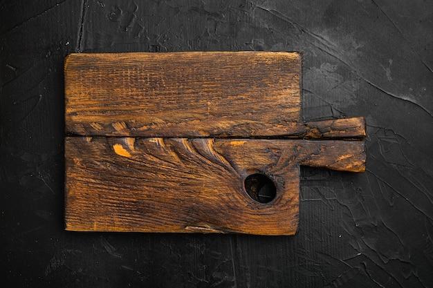 Zerkratztes schneidebrett-set, draufsicht flach, mit kopienraum für text oder essen, auf schwarzem hintergrund