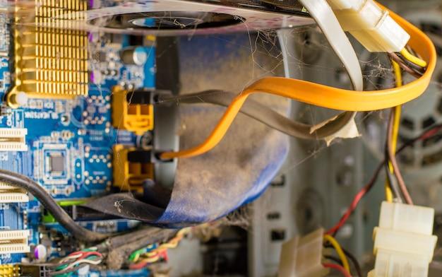 Zerlegter computer, drähte und leiterplatte in staub und spinnweben