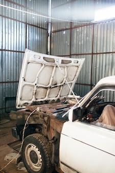 Zerlegtes weißes altes auto in der garage
