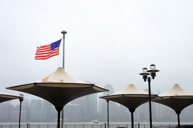 Zerlumpte amerikanische flagge, die im wind mit manhattan-skylinen auf hintergrund an einem regnerischen tag durchbrennt