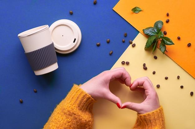 Zero waste coffee flat lag auf gespaltenem dreifarbigem papier, blau, orange und gelb. freundliche wiederverwendbare kaffeetassen eco, hände in der warmen winterstrickjacke, die herzzeichen zeigt.