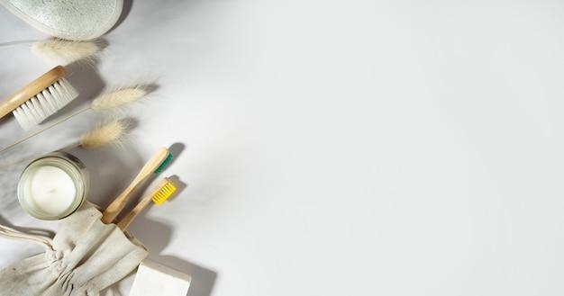 Zero waste concept.linen bag, bambuszahnbürsten, hölzerner ohrstöpsel, sojawachskerze auf glas. trendige schatten, weißer hintergrund. lagurus trockenblumen.umweltfreundlicher, nachhaltiger lebensstil.textfreiraum
