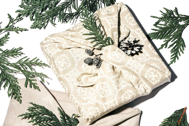 Zero waste geschenkverpackung im traditionellen japanischen furoshiki-stil. beige handgemachtes geschenkpaket für weihnachten mit stoff, thuja und kegel auf weiß. ökologisches konzept umweltfreundliches dekor weihnachten. nahaufnahme.