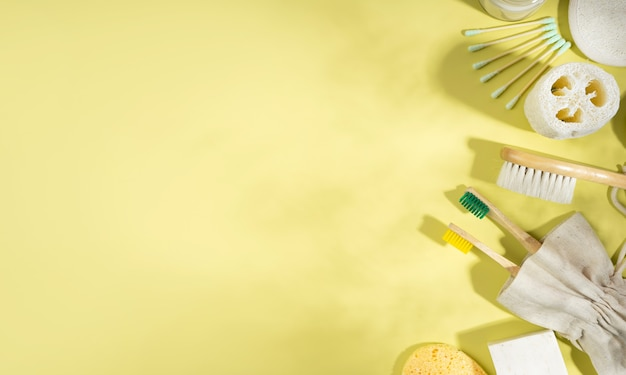 Zero-waste-konzept. leinenbeutel, bambuszahnbürsten, kamm, besteck, ohrstöpsel. trendige schatten auf gelbem hintergrund. ethischer, umweltfreundlicher, nachhaltiger lebensstil. ansicht von oben. flach legen. platz kopieren. banner