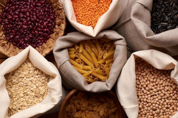 Zero waste-konzept. nüsse, getrocknete früchte, macarons und grütze in öko-baumwolltaschen und gläsern auf dem holztisch in der küche.