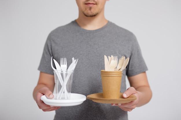 Zero waste und umweltfreundliches konzept - junger mann vergleicht plastik mit holz- und papiergeschirr auf grauem hintergrund