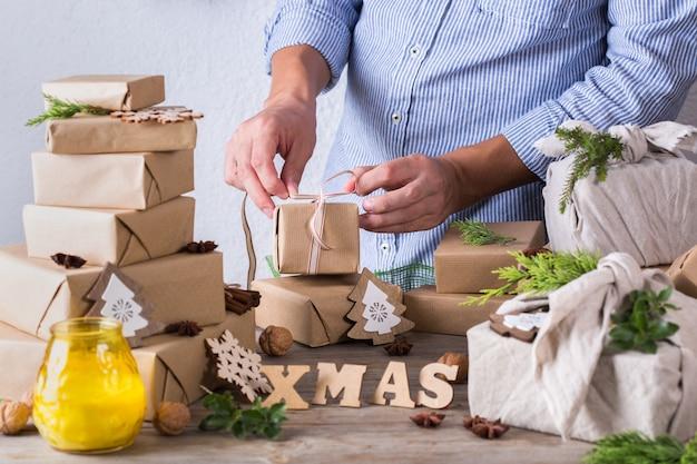 Zero waste weihnachtskonzept männliche hände, die geschenke verpacken
