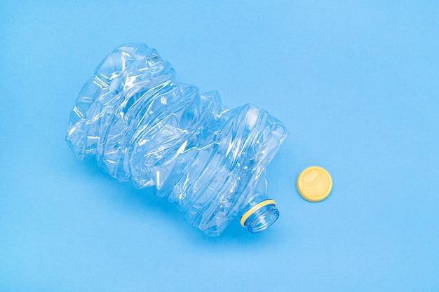 Zerquetschte plastikflasche lokalisiert auf blauem hintergrund. recycling-konzept. speicherplatz kopieren