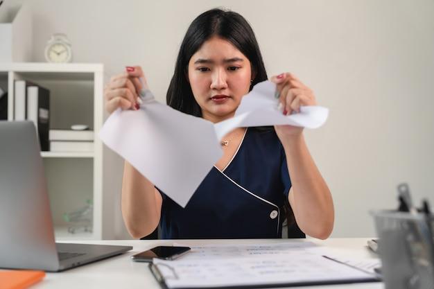 Zerreißendes papier der asiatischen geschäftsfrau verursacht durch erfolglose arbeit.