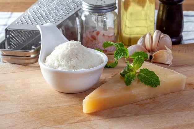 Zerriebener parmesankäseparmesankäse und metallreibe auf hölzernem brett