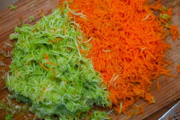 Zerrissene karotten und zucchini mit einer reibe