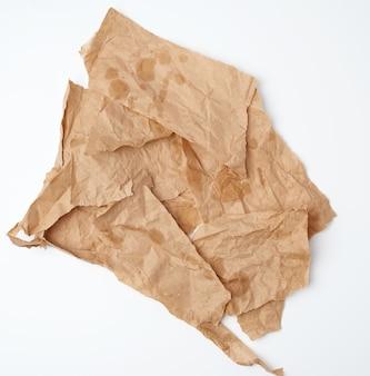 Zerrissene, zerknitterte, braune papierstücke mit fettflecken