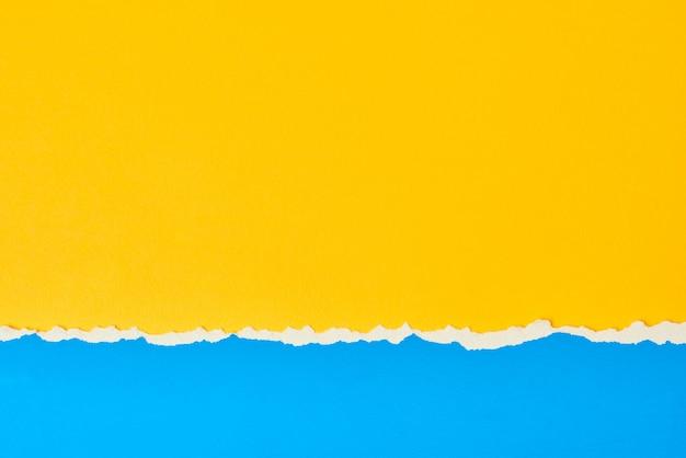 Zerrissene zerrissene papierkante mit einem kopierraum, farbe blau und gelber hintergrund