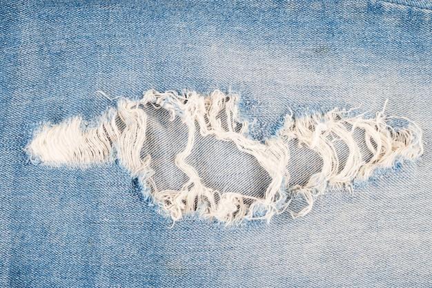 Zerrissener blue jeans-beschaffenheitshintergrund