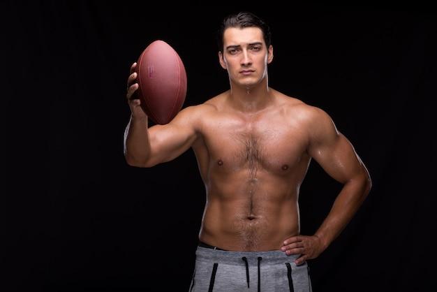 Zerrissener muskulöser mann mit amerikanischem fußball