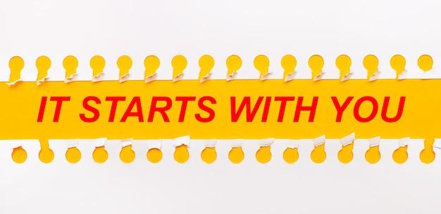 Zerrissener papierstreifen auf gelbem hintergrund mit text es beginnt mit dir