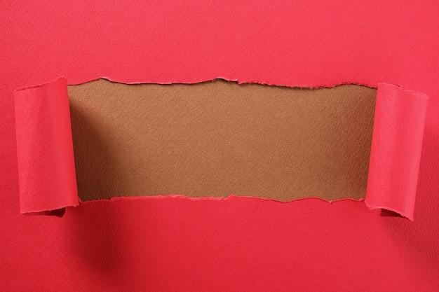 Zerrissener roter papierstreifen kräuselte den rand und deckte mittelbraunes backgroud auf