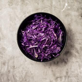 Zerrissener rotkohl in der schwarzen schüssel auf grau. vegetarisch gesundes essen. instagram draufsicht