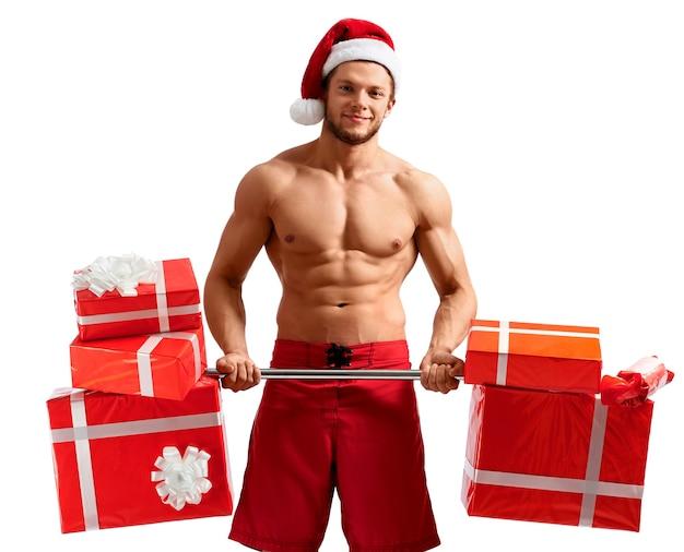 Zerrissener weihnachtsmann hält eine langhantel mit geschenken holding