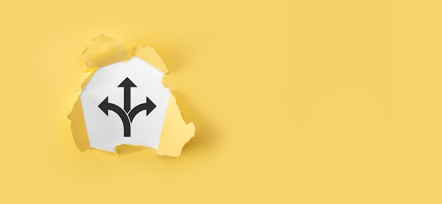 Zerrissenes gelbes papier mit baumrichtungssymbol auf weißer oberfläche