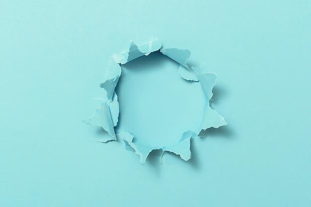 Zerrissenes loch in blauem papier mit kopierraum.