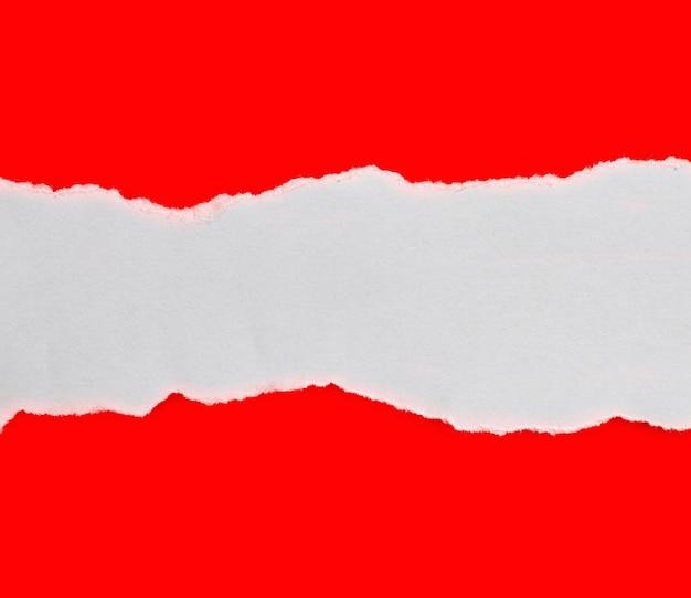 Zerrissenes papier auf rotem hintergrund isoliert