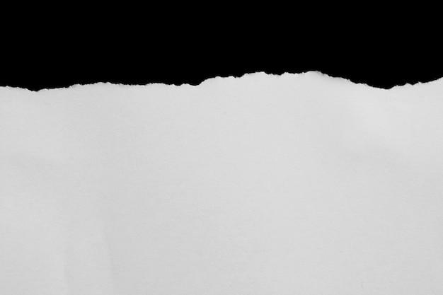 Zerrissenes papier auf schwarzem hintergrund mit kopienraum für text