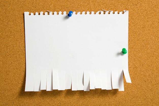 Zerrissenes papier durch druckbolzen an der pinnwand befestigt.