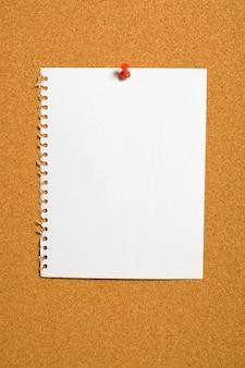 Zerrissenes papier mit rotem stoßstift an der pinnwand befestigt.