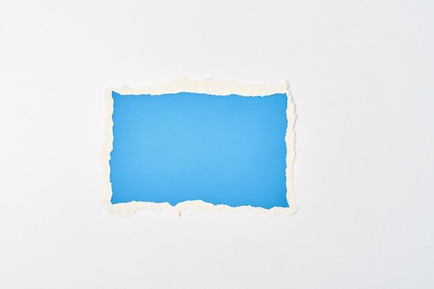 Zerrissenes randblatt des gerissenen blauen papiers auf weißem hintergrund. vorlage mit stück farbpapier