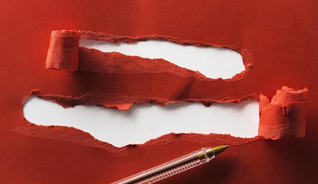 Zerrissenes rotes papier mit platz für ihren text und stift nahaufnahme