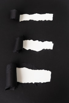 Zerrissenes schwarzes papier, das weiß aufdeckt