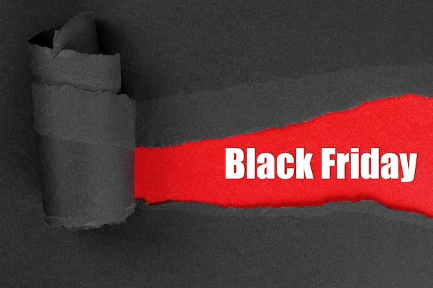Zerrissenes schwarzes papier mit schwarzer freitagsinschrift auf rot