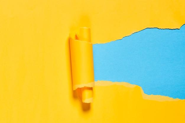 Zerrissenes und gerolltes stück gelbes papier über blauem hintergrund kopienraum heller und kreativer hintergrund