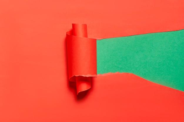 Zerrissenes und gerolltes stück rotes papier über grünem hintergrund kopienraum heller und kreativer hintergrund