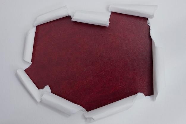 Zerrissenes weißbuch über hintergrund der roten farbe.