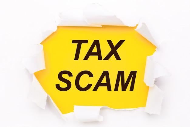 Zerrissenes weißes papier liegt auf einem leuchtend gelben hintergrund mit dem text tax scam