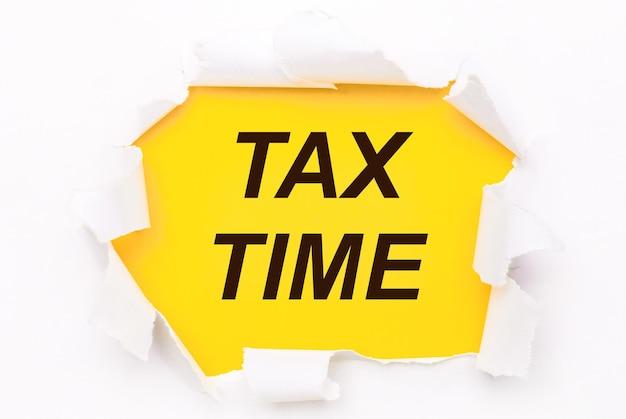 Zerrissenes weißes papier liegt auf einem leuchtend gelben hintergrund mit dem text tax time