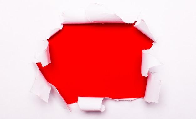 Zerrissenes weißes papier liegt auf einer roten oberfläche. speicherplatz kopieren