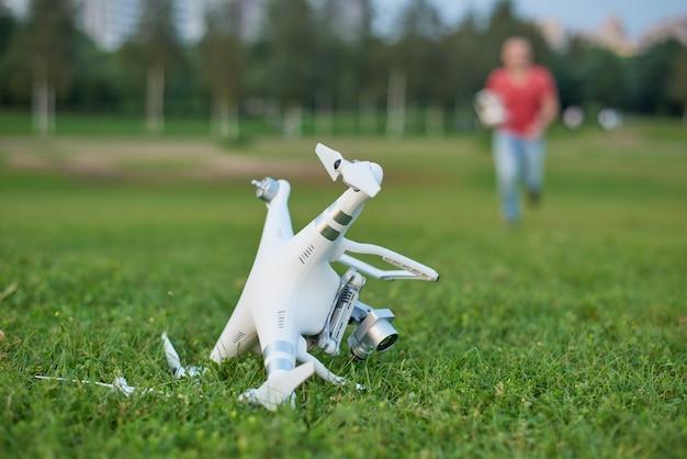 Zerschmetterter quadrocopter im park. propellerschaden. bediener läuft