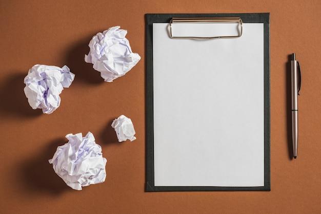 Zerschmettertes papier, stift mit leerem papier auf klemmbrett gegen farbigen hintergrund