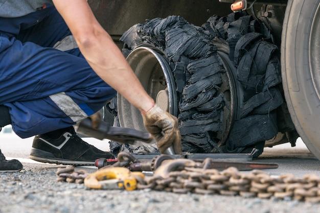 Zerstörter geblasener reifen mit zerquetschtem und beschädigtem gummi auf einem lkw.