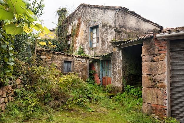 Zerstörtes verlassenes haus in spanien, europa. zerbrochene fenster, beschädigte wände und verwachsener garten.