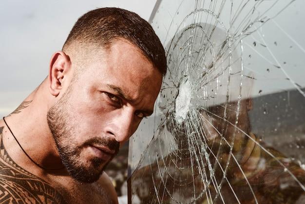 Zerstörung des gehirns. quetschtest. der diebstahl. emotionale entladung. wut. zerstörung. sexy hispanischer mann zerbrochener spiegel. einschussloch im glas. glasscherben wegen schlag. macho-mann hinter zerbrochenem glas.