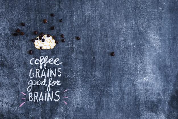 Zerstreute kaffeebohnen auf papierausschnittgehirn mit text auf tafel