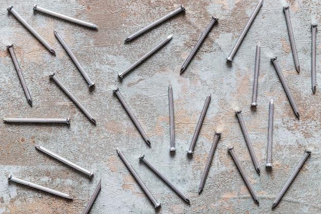Zerstreute nägel auf hölzernem schreibtisch des schmutzes