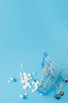 Zerstreute pillen, tabletten und kapseln der pharmazeutischen medizin auf dem dollargeld lokalisiert auf blauem hintergrund. medikamentenkosten.