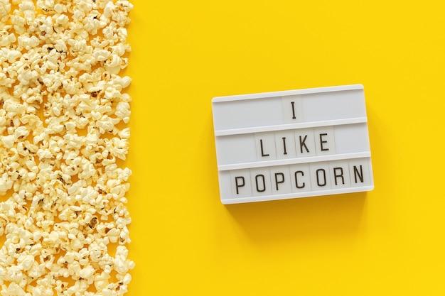 Zerstreuter popcornrand linker rand und leuchtkasten-text mag ich popcorn auf gelbem papierhintergrund.