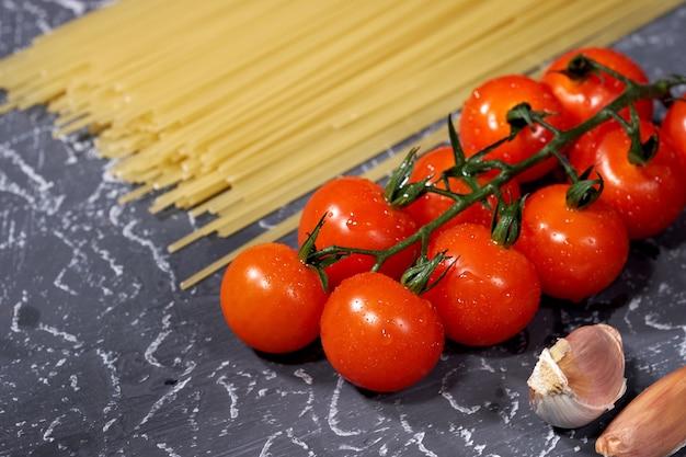 Zerstreuter spaghettiknoblauch, tomaten, auf grauem hintergrund